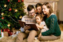 Friendly family offour reading interesting book in the evening Stock Photos