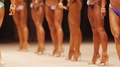 Women with beautiful tanned fit bodies walking on stage, fitness competition HD Footage