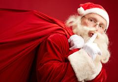 Santa with heavy sack showing shh gesture Stock Photos