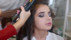 Make up artist applying eyeshadows while hairdresser making hair-do slow motion Stock Footage