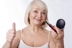 Delighted senior woman holding mascara Stock Photos
