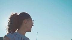Beautiful young girl in sunglasses talking on the field. sunlight glare and Stock Footage