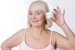 Cheerful senior woman holding a cream bottle Stock Photos