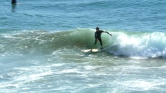 Surfer catches wave on surf beach in California Stock Footage