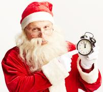 Santa showing time in alarm-clock and looking at camera Stock Photos