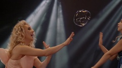 Woman and little girl is doing soap bubble show on the black background Stock Footage