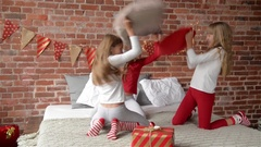 Happy laughing Triplets sisters in pajamas having a pillow fight in bed at home Stock Footage