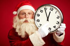Santa Claus pointing at face of clock showing five minutes to midnight Stock Photos