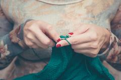 Manicured woman hands knitting green plaid, warm vintage Stock Photos