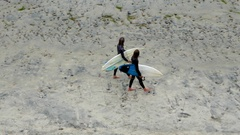 Teen surfers in wet suits carry surfboards on beach Stock Footage