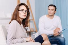Troubled woman having a consultation with psychologist Stock Photos