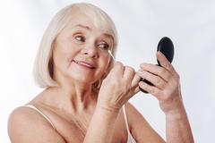 Positive senior woman looking into the mirror Stock Photos