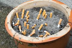 Outdoor ashtray with sand and cigarettes Stock Photos
