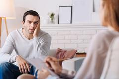 Pleasant moody man talkign with professional psychologist Stock Photos