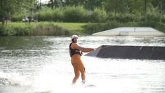 Wakeboarder in orange wetsuit cruising by [Slomo] Stock Footage