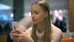 Beautiful girl in turtleneck sitting in a cafe and texting on smartphone Stock Footage