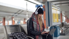 Girl with headphones receives message on smartphone while using laptop Stock Footage