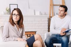 Distressed young woman consulring with psychologist Stock Photos