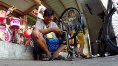 Repairman aligning the wheel of  a motorcycle Stock Footage