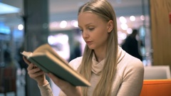 Pretty, blonde girl answers cellphone while reading book in the cafe Stock Footage