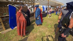 Characters from medieval times are stopping at a stand with a drink Stock Footage