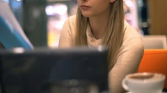 Occupied girl looking on notes and typing something on laptop, steadycam shot Stock Footage