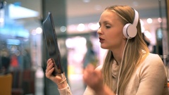 Girl looking absorbed while having a videocall on tablet in the cafe Stock Footage