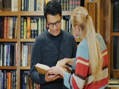 Asian man with glasses and Caucasian women standing together watching the book Stock Footage
