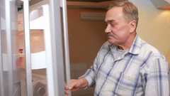 Senior man opens the fridge and drink the juice from the package. It quenches Stock Footage
