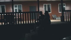Young couple sitting on the front porch and talking Stock Footage