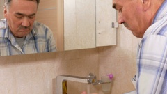 Man aged washes his hands with soap in the bath. He rinses his hands with water Stock Footage