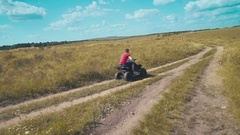 A brave guy goes fast on an ATV on the field Stock Footage
