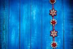 Ribbon with felt snowflakes on a blue wooden surface Stock Photos