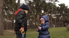 A one year old girl kissing a dandelion. A three year old boy standing close by Stock Footage