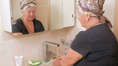 Senior woman washes his hands with soap in the bath. It can be seen reflected in Stock Footage