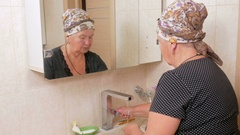 Woman aged wash your face with soap in the bath. It can be seen reflected in a Stock Footage