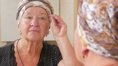 Woman aged plucks eyebrows in the bath. It can be seen reflected in a mirror box Stock Footage