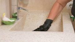 Senior woman cleans the sink in the bathroom of the hotel room. She uses gloves Stock Footage