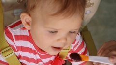Baby sitting in Feeding table. sitting in chair and eating Stock Footage