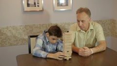 Dad and son playing board game Jenga Stock Footage