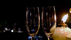 Pouringshampagne in a glass at night party outside, candle beside it Stock Footage