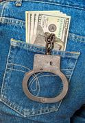 Black metal handcuffs and american currency in back jeans pocket Stock Photos