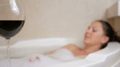 Beautiful girl taking a bubble bath with a glass of wine. A large white bath and Stock Footage