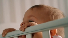 Incredibly beautiful and cute little girl stands in crib Stock Footage