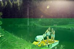 Three adult female friends launching rowing boat on lake, Sattelbergalm, Tirol, Stock Photos