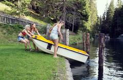 Three adult female friends launching rowing boat into lake, Sattelbergalm, Stock Photos