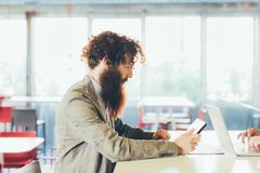Young male hipster with curly hair and beard using digital tablet at desk Stock Photos
