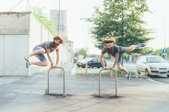 Identical adult male twins kicking up heels on sidewalk Stock Photos