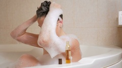 A young girl takes a bath with foam and washing hair with shampoo. A large white Stock Footage
