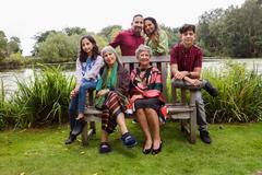 Portrait of four generation family, beside lake, smiling Stock Photos